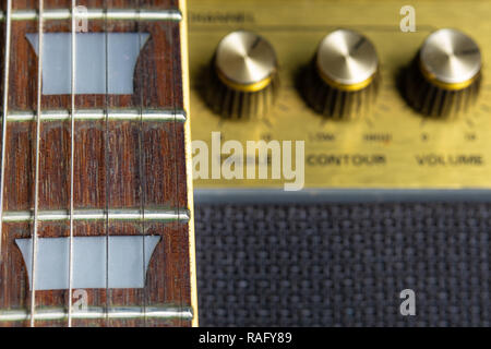 guitar fretboard and fret marker detail, blurred old amplifier knobs in the background - Stock Image
