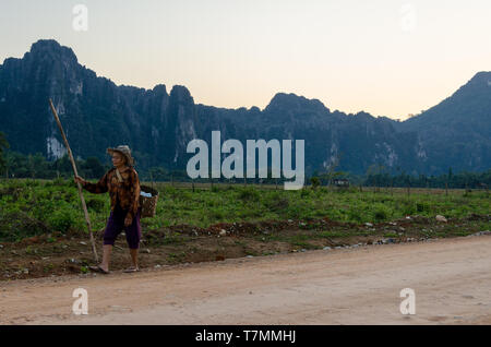 A Farmer walks back home after a day in the field, Vang Vieng, Laos - Stock Image