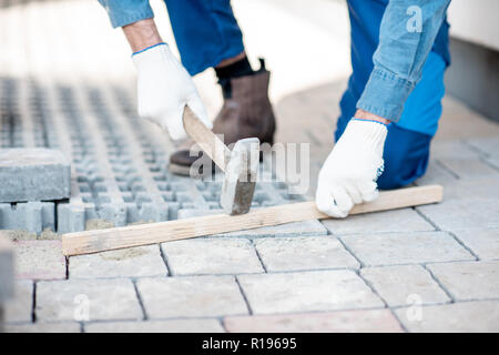 Builder laying paving tiles on the construction site, close-up view with no face - Stock Image