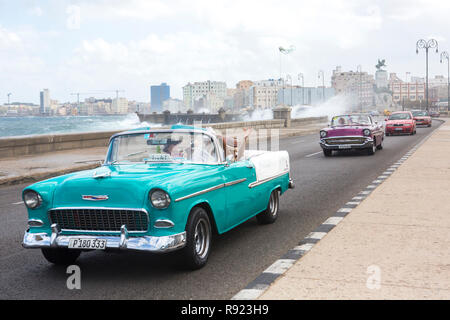 People driving turquoise vintage car passing waves splashing against malecon, Havana, Cuba - Stock Image
