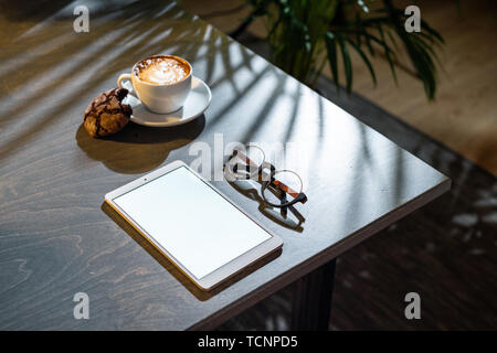 Close up of white coffee cup, oat cookies, glasses and pad with blank screen on dark wooden table with tropic plant on background. - Stock Image