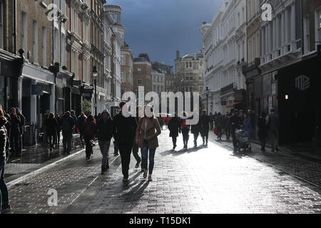 People walking in street backlit, Covent Garden, London, England, UK - Stock Image
