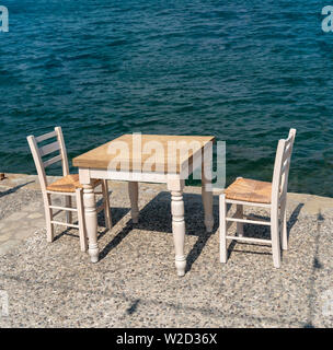Ierapetra, Crete, Greece. June 2019. Table and two chairs set customer use on the quayside at this southern Crete resort. - Stock Image