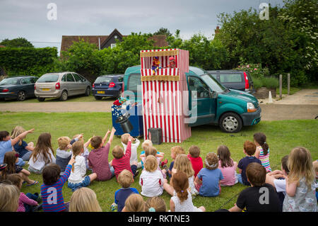 Children enjoy the traditional Punch & Judy Show at Great Milton Fete, Oxfordshire. - Stock Image