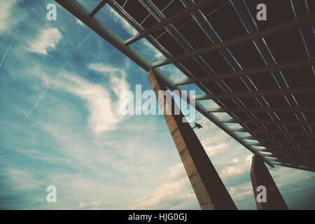 Wide angle view of modern hi-tech solar photovoltaic panel with empty space for your message on the left on sky, - Stock Image