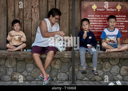 Grandmother taking care of grandchildren at a street food market and providing fruit and ice cream treats. Thailand, Southeast Asia - Stock Image