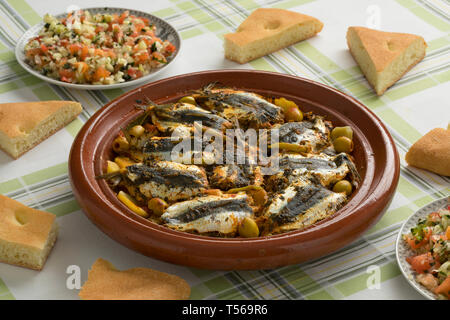 Traditional  Moroccan Tagine with stuffed sardines, salad and bread on the table for dinner - Stock Image
