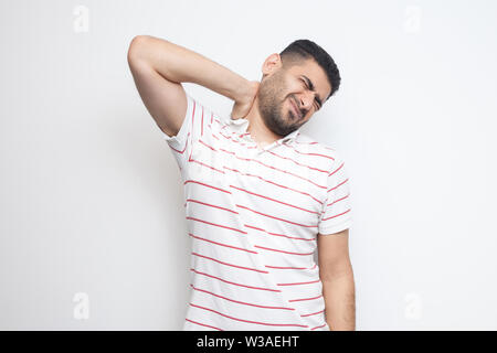 Neck ache or pain. Portrait of handsome bearded young man in striped t-shirt standing and holding his painful neck. indoor studio shot, isolated on wh - Stock Image
