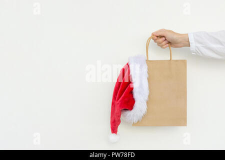 Young caucasian woman holds in hand empty blank mock up brown craft paper bag with hanging santa claus hat on white wall background. Christmas New Yea - Stock Image