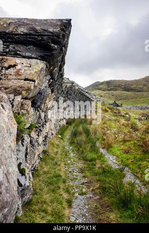 Overhanging wall above old tram lines in disused Gorseddau slate quarry in Snowdonia National Park. Cwmystradllyn Porthmadog Gwynedd Wales UK Britain - Stock Image