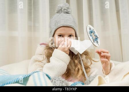 Kid girl sneezes in a handkerchief at home, The season is autumn winter. - Stock Image