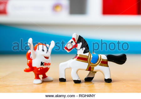 Poznan, Poland - January 20, 2019: Plastic Kinder egg toy figure raising his hands in happiness in front of a wooden small horse in soft focus backgro - Stock Image