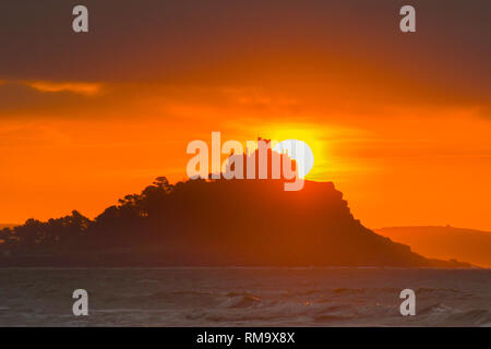 Penzance, Cornwall, UK. 14th Feb, 2019. UK Weather. It was a mild and colourful sunrise at Penzance this morning, with the temperature allready above 10 degrees C at 7.30am. The sun seen here rising behind St Michaels mount at Marazion. Credit: Simon Maycock/Alamy Live News - Stock Image