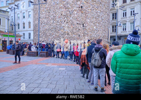 Long line-up of people waiting in line to visit the Galata Tower on a cold winter day. Istanbul, Turkey - December - Stock Image