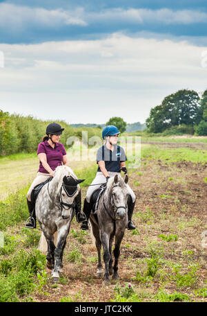 Two young girls out riding horses on a late summers afternoon - Stock Image