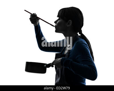 one  woman cooking tasting saucepan in silhouette studio isolated on white background - Stock Image