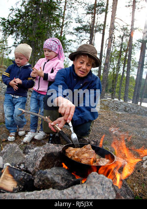 Family cooking over fire - Stock Image