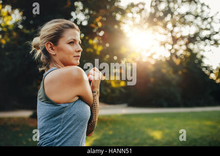 Portrait of fitness woman stretching arms in the park. Caucasian female working out in the morning. - Stock Image