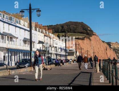 Sidmouth, Devon. 2nd Nov 2018. UK Weather: Visitors walk on the Esplanade at Sidmouth in bright sunshine. Photo Central/Alamy Live News - Stock Image