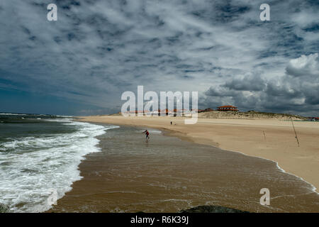 Fisherman surfcasting on the empty shore of a french tourist spot. - Stock Image