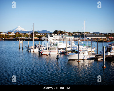 Perfect cone volcano: Mount Egmont, Taranaki. New Plymouth harbour. New Zealand. Boat names and logos removed. - Stock Image