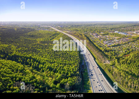 Traffic on the highway road  running to the horizon, forest and rural housing aerial panoramic landscape at summer day - Stock Image