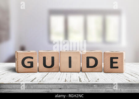 Guide sign made of wood on a desk in a bright room with windows - Stock Image
