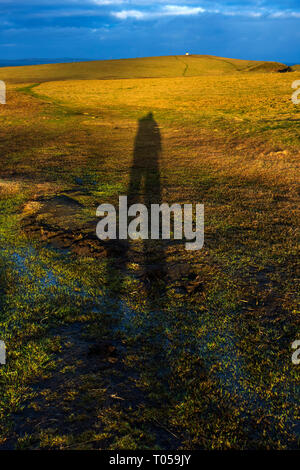 Shadow of a walker pointing towards the lighthouse on Duncansby Head, Caithness, Scotland, UK - Stock Image