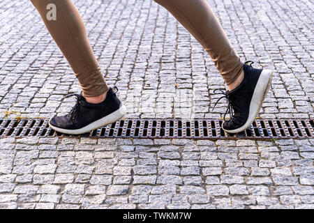 running, close up of a woman's legs and feet while jogging outside - Stock Image