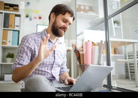Bearded casual businessman with laptop waving his hand while talking to someone through video chat in office - Stock Image
