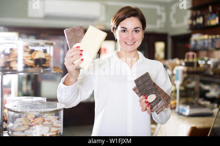 Smiling girl deciding on best bar of chocolate in confectionery - Stock Image