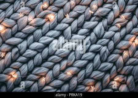 Christmas lights on warm woolen sweater,Closeup - Stock Image