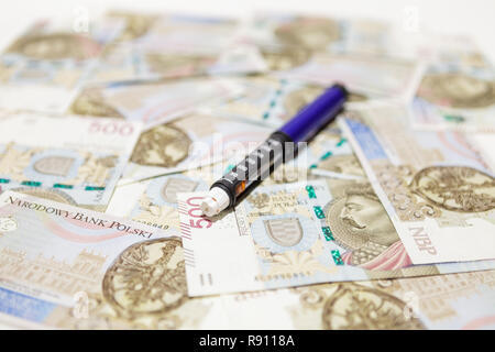 Pen injector on polish money banknotes 500 PLN - Stock Image