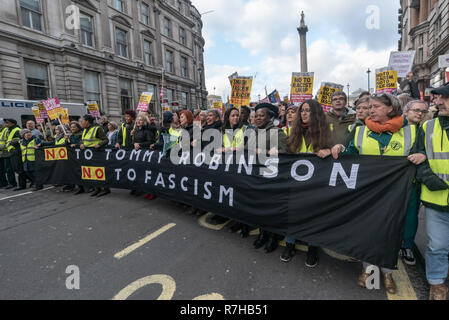 London, UK. 9th Dec, 2018. The A united counter demonstration by anti-fascists marching in opposition to Tommy Robinson's fascist pro-Brexit march reaches Whitehall behind the main banner 'No to Tommy Robinson, No to Fascism' carried by women. Police had issued conditions on both events designed to keep the two groups well apart. Credit: Peter Marshall/Alamy Live News - Stock Image