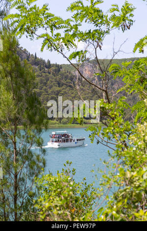 Krka National Park, Croatia. A small boat with tourists on the Krka River. - Stock Image
