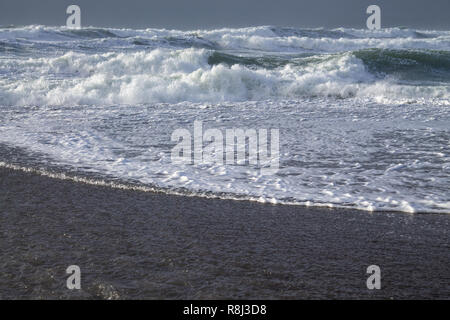 waves rolling onto beach or shoreline - Stock Image