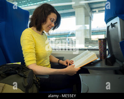 young attractive woman loking in book and reading during traveling in train - Stock Image