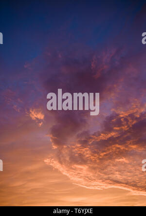 Dramatic pink, purple and orange clouds at sunset - Stock Image