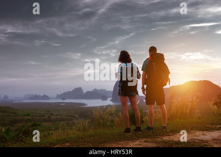 Couple of backpackers stands at sunrise or sunset at sea and islands backdrop. Tourism concept - Stock Image