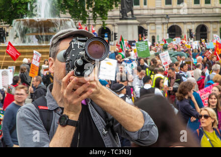 A film maker using 35mm film shoots footage of the protestors at Trafalgar Square demonstrate against the state visit of Donald Trump - Stock Image