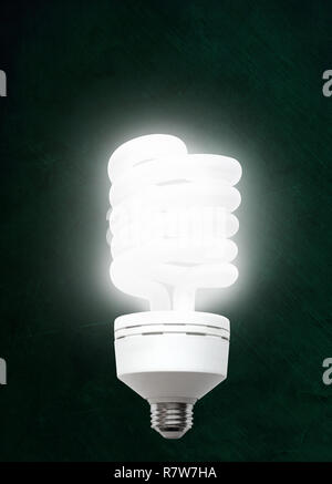 Illuminated CFL compact fluorescent light bulb against chalkboard background with copy space. - Stock Image