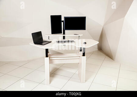 An office table with two manitors, a lifting mechanism for the holder of the manitor and a tabletop behind which you can work standing and sitting. A  - Stock Image