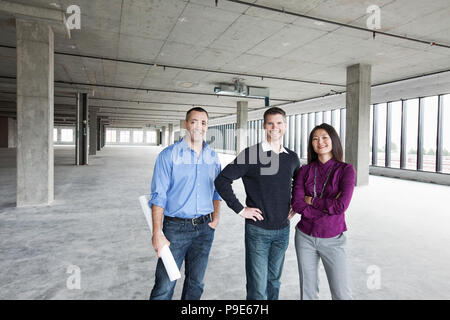 An architect and two owners of a new raw business space standing in a line. - Stock Image