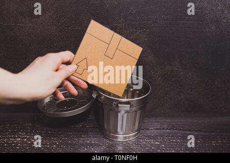 mini cardboard box going into a garbage bin, concept of recycling or excessive shopping - Stock Image