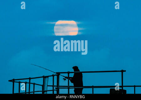 Man fishing with moon rising in a cloudy sky above - Stock Image