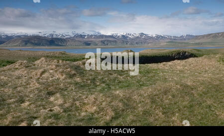 View inland from high ground ,Dyrholaey,Iceland of a landscape with sea and mountain range - Stock Image