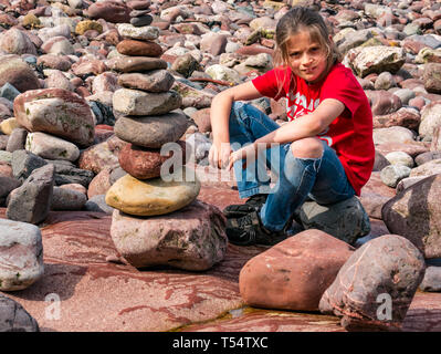 Dunbar, East Lothian, Scotland, UK. 21st Apr 2019. European stone stacking championship:  Alijah, from Wales, with his winning stone stack in the Quantity competition for children under 15 years of age –- most stones balanced vertically - at Eye Cave beach on the second day which comprises 2 competitions, a 3 hour artistic challenge and a children's competition. The overall winner receives a trip to llano Earth Art Festival & World Stone Balancing competition in Texas in 2020. Credit: Sally Anderson/Alamy Live News - Stock Image