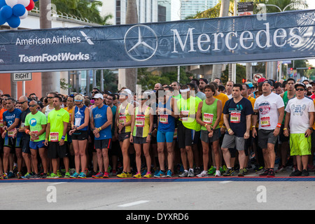 First-place winners Tyler McCandless and Kristen Arendt wait with other runners at start of 2014 Mercedes Benz Corporate Run. - Stock Image