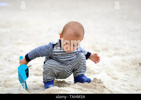 Adorable Baby Boy Playing With Sand And Blue Plastic Shovel On The Beach - Stock Image