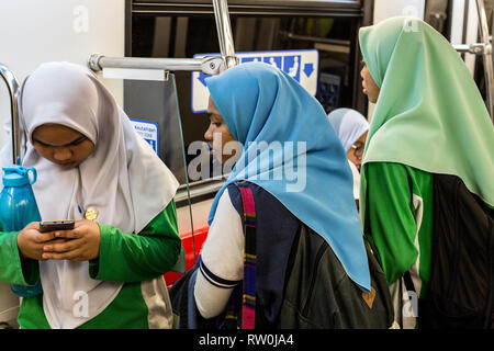 Teenage Malaysian Girls in Typical Modest Muslim  Dress Waiting to Board a Bus, Kuala Lumpur, Malaysia. - Stock Image